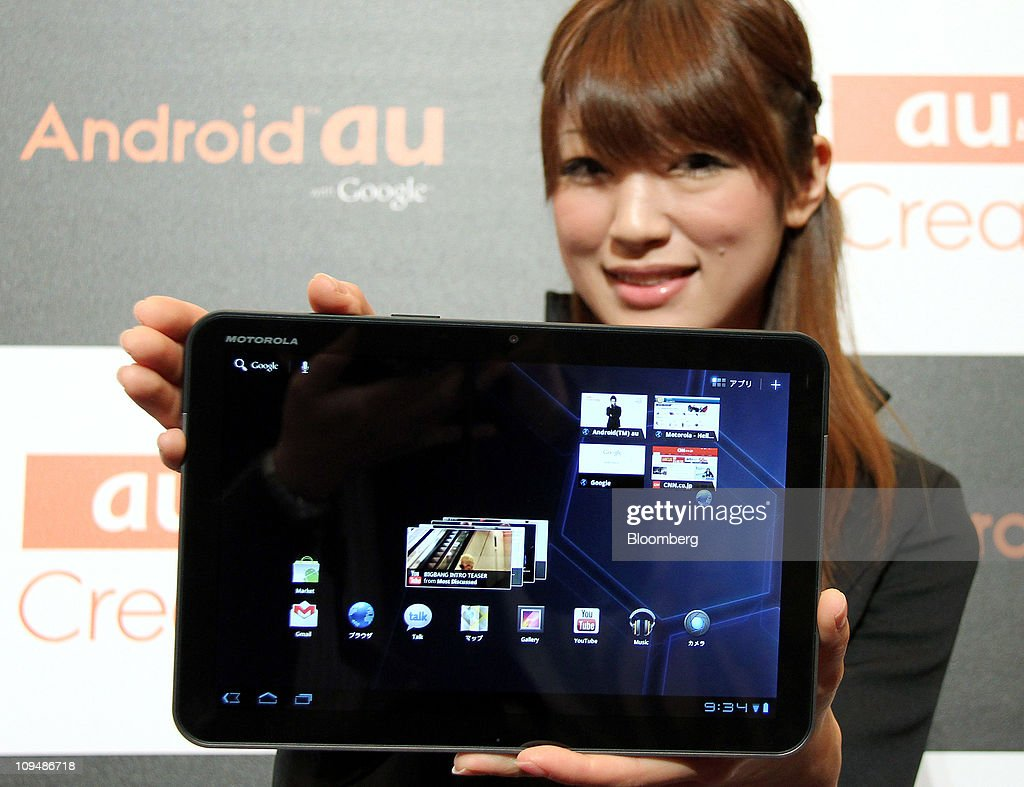 A model for KDDI Corp. poses with a Motorola XOOM tablet device manufactured by Motorola Mobility Inc., during an unveiling in Tokyo, Japan, on Monday, Feb. 28, 2011. KDDI is Japan's second-largest mobile-phone operator. Photographer: Haruyoshi Yamaguchi/Bloomberg via Getty Images