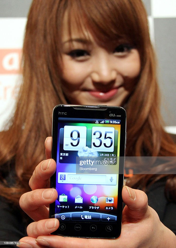 A model for KDDI Corp. poses with an htc EVO WiMAX smartphone manufactured by htc Corp., during an unveiling in Tokyo, Japan, on Monday, Feb. 28, 2011. KDDI is Japan's second-largest mobile-phone operator. Photographer: Haruyoshi Yamaguchi/Bloomberg via Getty Images