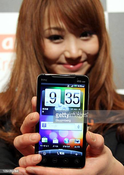 A model for KDDI Corp poses with an htc EVO WiMAX smartphone manufactured by htc Corp during an unveiling in Tokyo Japan on Monday Feb 28 2011 KDDI...