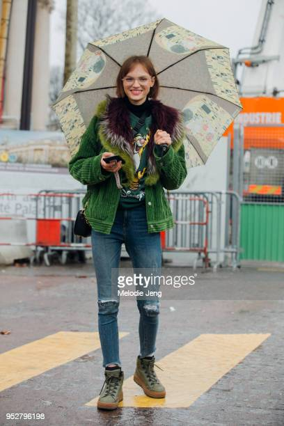 Model Fran Summers carries a Gustav Klimt umbrella holds her phone and wears oversized glasses a green corduroy jacket with a fur lining a green...