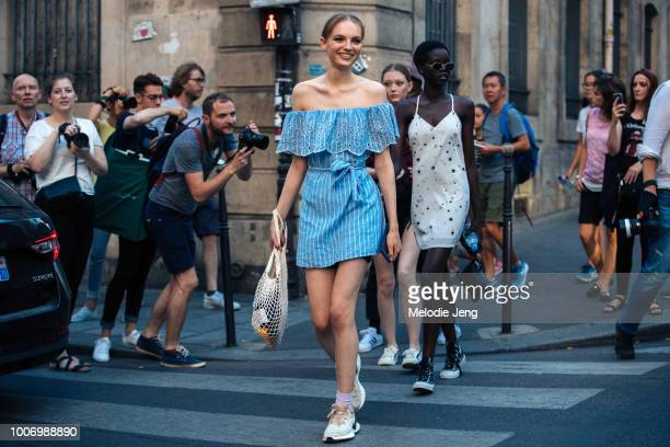 Model Fran Summers exits the Givenchy show in a blue offshoulder summer dress white net bag and white sneakers during Couture Fall/Winter 2018...