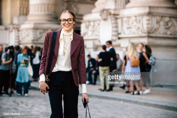 Model Fran Summers exits the Paco Rabanne show at Grand Palais in a red patterned blazer white top blue pants black boots and oversized glasses...