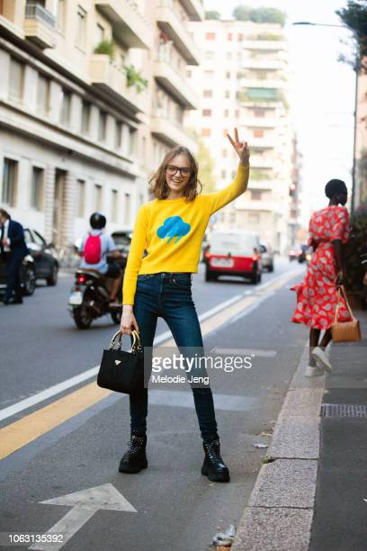 Model Fran Summers gestures a peace sign and wear a white sweater with a rain cloud blue jeans black Prada purse and black chunky boots during Milan...