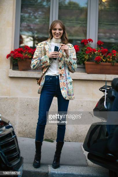 Model Fran Summers wears a brocade print jacket white top blue jeans and black boots after the Valentino show during Paris Fashion Week Spring/Summer...