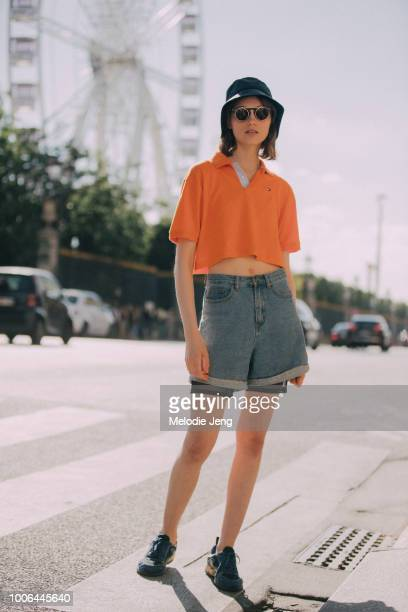 Model Fran Summers wears a bucket hat circle flip up sunglasses a cropped orange Tommy Hilfiger polo jean shorts and black sneakers after the...