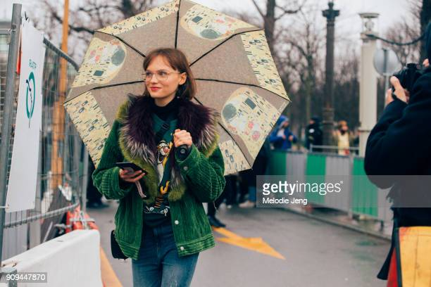 Model Fran Summers wears a green corduroy jacket with fur lining a Disney tiger sweatshirt and a Gustav Klimt umbrella outside the Chanel show at...