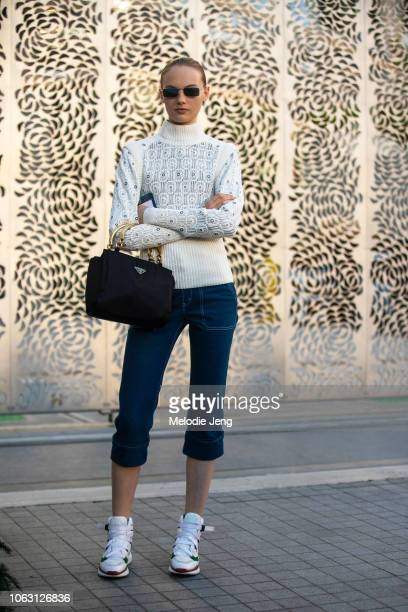 Model Fran Summers wears a white embroidered sweater black Prada bag cropped black pants white chunky sneakers after the Burberry show during London...