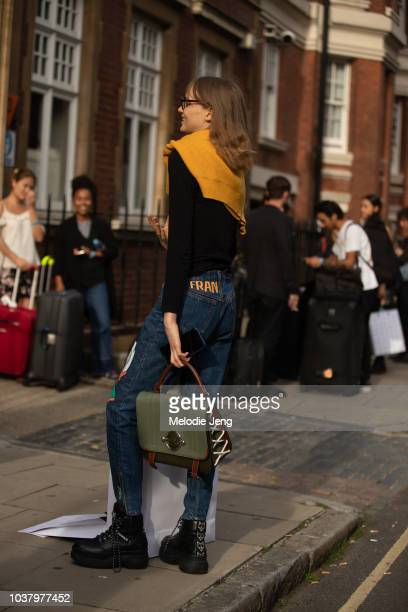 Model Fran Summers wears a yellow sweater Fran customized jeans and a green JW Anderson bag during London Fashion Week September 2018 on September 13...