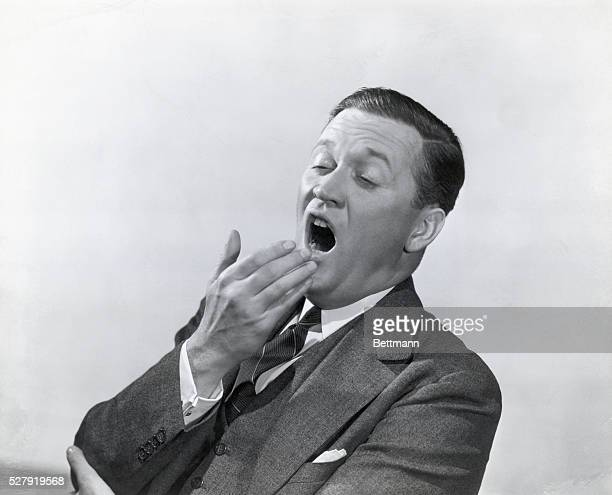 Model Frank Kelly, in a suit and tie, tries to cover his mouth as he yawns. Undated photograph.