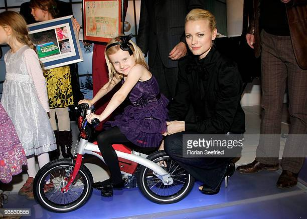 Model Franziska Knuppe and child pose on stage at the launch of the BMW art advent calender 2009 at a BMW branch on December 1, 2009 in Berlin,...