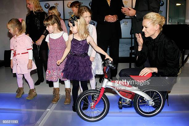 Model Franziska Knuppe and children pose on stage at the launch of the BMW art advent calendar 2009 at a BMW branch on December 1, 2009 in Berlin,...