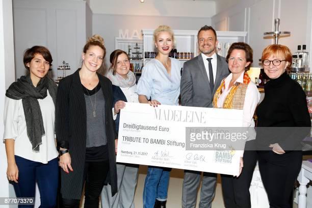 Model Franziska Knuppe with Ines Dang Katrin Matuschek Melanie Zemanek Franziska Knuppe Volker Valk Johanna Ruoff and Britta Wilkens hands over the...