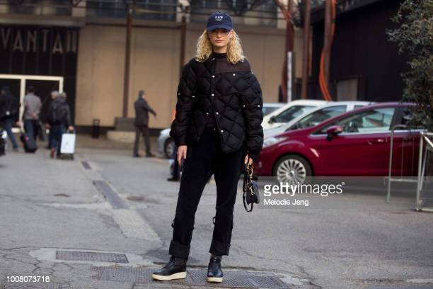 Model Frederikke Sofie in a blue TSW LLC cap black assymetrical open shoulder down jacket black pants black Celine shoes and a small Chloe purse...