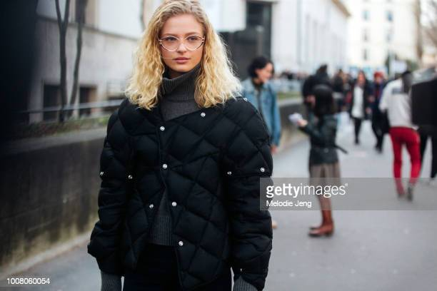 Model Frederikke Sofie wears glasses a black asymmetrical quilted down jacket and gray sweater during Paris Fashion Week Fall/Winter 2017 on March 2...