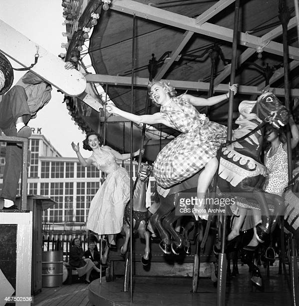 Model from the CBS gameshow The Big Payoff Cindy Robbins grabs the brass ring on the carousel at Steeplechase Park Pat Conway is behind her Image...