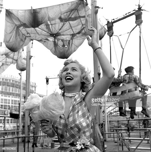 Model from the CBS gameshow The Big Payoff Cindy Robbins with cotton candy at Steeplechase Park Coney Island Brooklyn NY Image dated May 11 1953