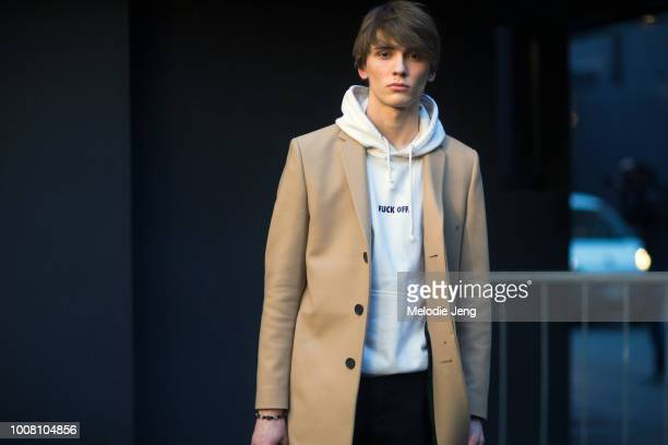 Model Gabriel Besnard wears a cream jacket and white 'Fuck Off' hoodie after MSGM during Milan Men's Fashion Week Fall/Winter 2017/18 on January 16...