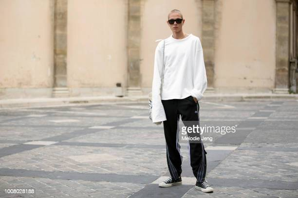 Model Genadij Wilen wears black sunglasses an extralong sleeve white shirt black Adidas trackpants and black Converse sneakers after the Thom Browne...