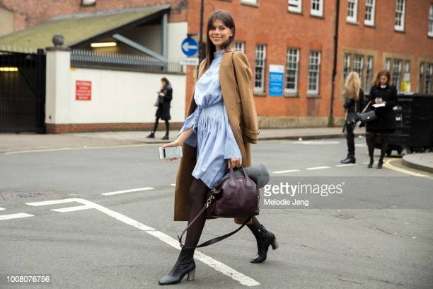Model Georgia Fowler wears a camel peacoat light blue shirtdress purple Givenchy bag and black boots while waiting for her Uber shown on her iPhone...