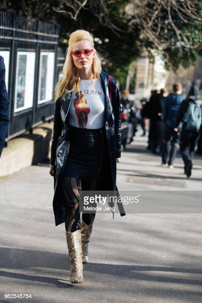 Model Georgia May Jagger wears red 70s style sunglasses a long blue leather jacket a Queen tshirt black leather skirt tights and python boots after...