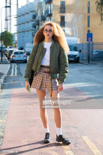 Model Georgia Moot wears a vintage Miu Miu skirt, Acne bomber jacket, LA Apparel T shirt and Salomon trainers during LFW September 2020 at on...