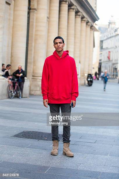 Model Geron McKinley wears a red hoodie over a gray tshirt blcak jeans and tan boots after the Hermes show on June 25 2016 in Paris France