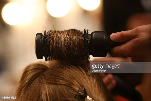 A model gets her hair done backstage ahead of the Shai Shalom show during the MercedesBenz Fashion Week Berlin Spring/Summer 2016 at Brandenburg Gate...