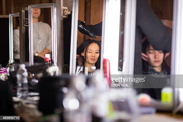 A model gets her hair dried backstage ahead of the catwalk show of London based fashion label Fyodor Golan at the Fashion Scout venue during the 2015...