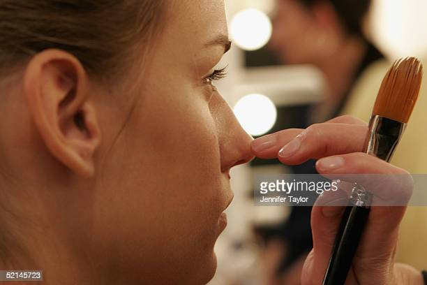 A model gets her makeup applied backstage at the presentation of the Thakoon Fall 2005 show during Olympus Fashion Week at DriveIn Studios February 6...