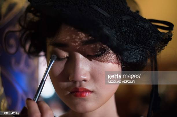 A model gets her makeup done backstage before displaying creations from designer Grace Chen on the