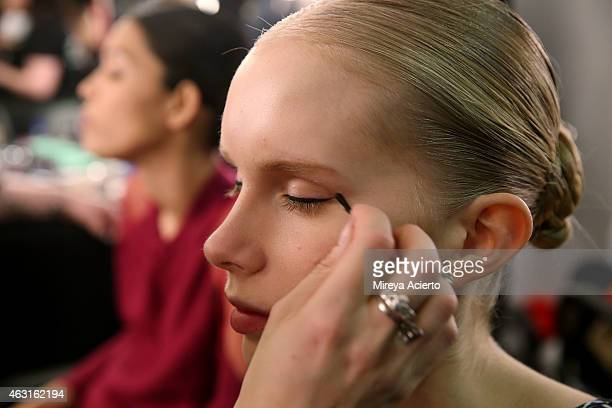 A model gets makeup applied backstage at the Epson Digital Couture presentation during MercedesBenz Fashion Week Fall 2015 at Industria Studios on...
