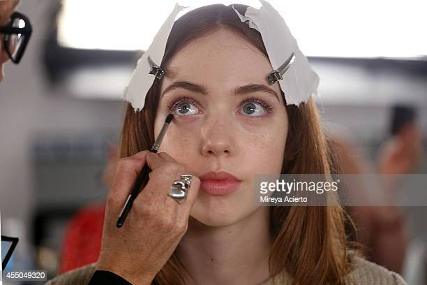 A model gets makeup applied backstage at the Timo Weiland Women's runway show during MADE Fashion Week Spring 2015 at Milk Studios on September 9...