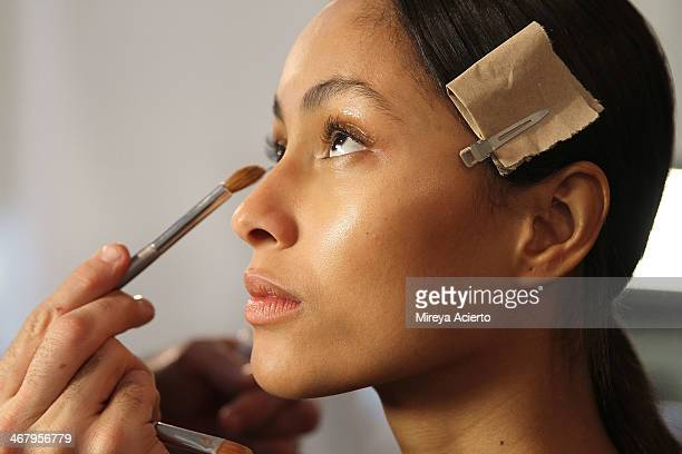 A model gets makeup applied backstage the Ostwald Helgason fashion show during MADE Fashion Week Fall 2014 at Milk Studios on February 8 2014 in New...