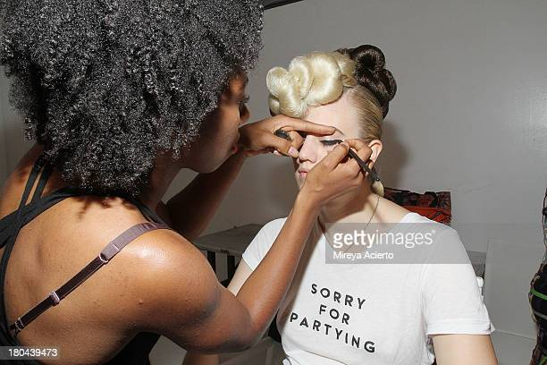 A model gets makeup backstage at the St Wobil fashion show during MercedesBenz Fashion Week Spring 2014 at The Designer's Loft at Studio 450 on...