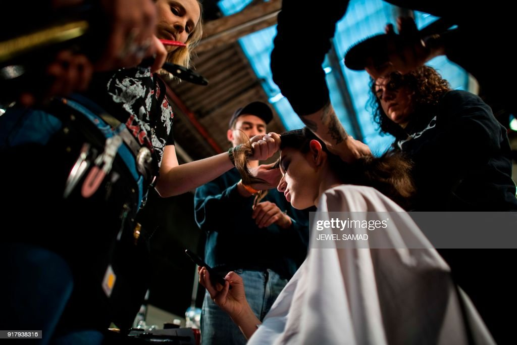 A model gets ready backstage to present creations by Hugo Boss during the New York Fashion Week on February 13, 2018, in New York. / AFP PHOTO / Jewel SAMAD