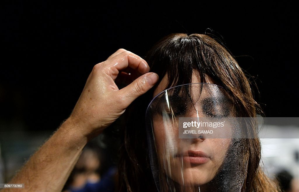 A model gets ready backstage to present Tadashi Shoji designs during the Fall 2016 New York Fashion Week at the Arcat Moynihan Station on February 12, 2016, in New York. / AFP / JEWEL