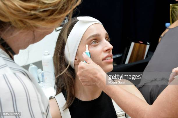 A model gets styled with a Pili Ani product backstage at the Tadashi Shoji show at New York Fashion Week The Shows at Spring Studio on September 6...
