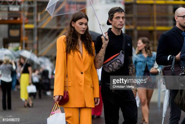 Model Giannina Mueller wearing a red Gucci bag yellow orange suit and Carl Jakob Haupt outside Marina Hoermanseder during the MercedesBenz Fashion...