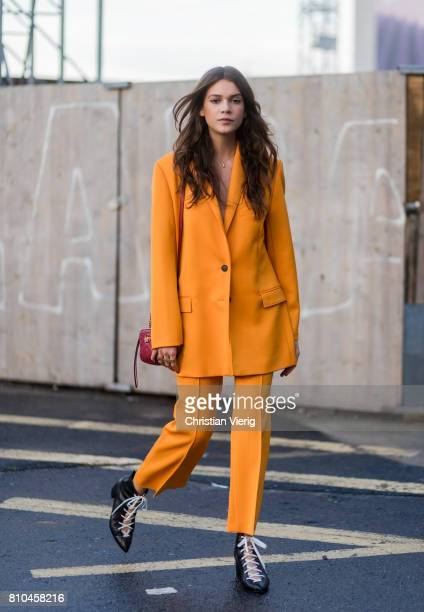 Model Giannina Mueller wearing a red Gucci bag yellow orange suit outside Marina Hoermanseder during the MercedesBenz Fashion Week Berlin...