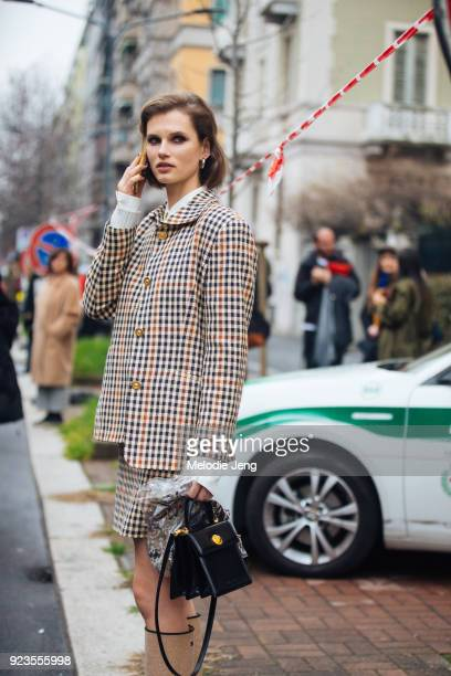 Model Giedre Dukauskaite talks on the phone and wears a matching gingham blazer and skirt carries a black Bulgari bag and wears Chanel boots during...