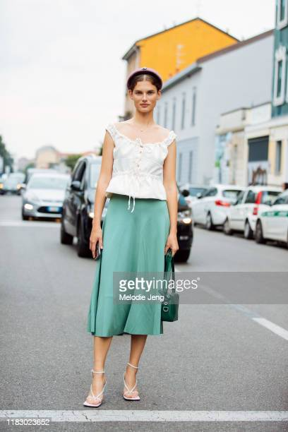 Model Giedre Dukauskaite wear a pink headband white sleeveless top green skirt green bag and white heels after the Fila show during Milan Fashion...