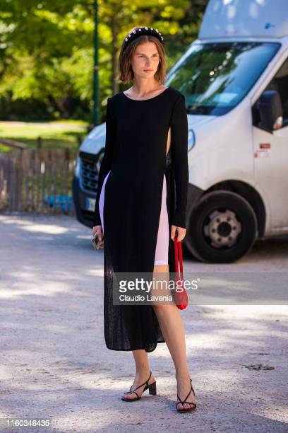 Model Giedre Dukauskaite wearing a black long top white biker shorts black sandals red bag and black hairband is seen outside Alexandre Vauthier show...