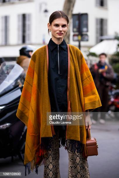 Model Giedre Dukauskaite wearing a black shirt big orange and tan scarf snake printed trousers and tan bag is seen in the streets of Paris before the...