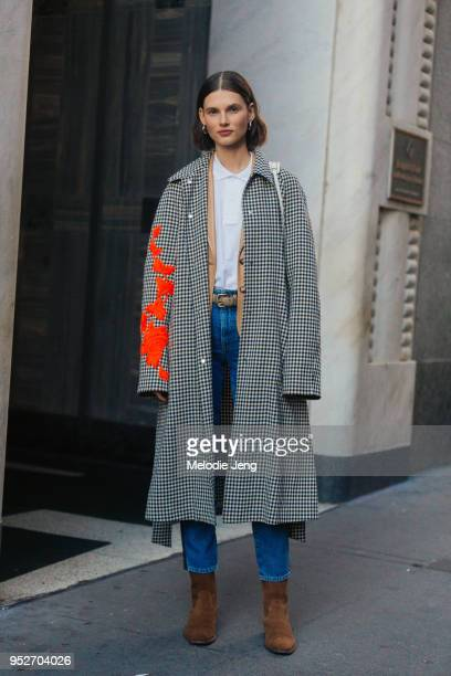 Model Giedre Dukauskaite wears a black and white gingham coat with orange floral embellishment a white top blue jeans and brown suede Saint Laurent...