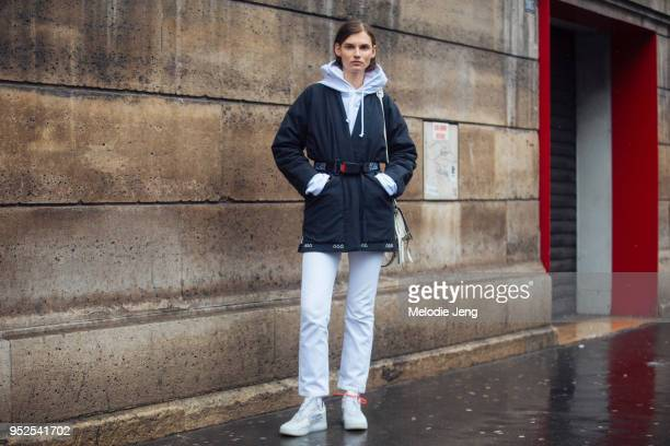 Model Giedre Dukauskaite wears a black jacket a KAR belt a white L'art de l'automobile hoodie white jeans and white OFF–WHITE x Nike Air Force 1...