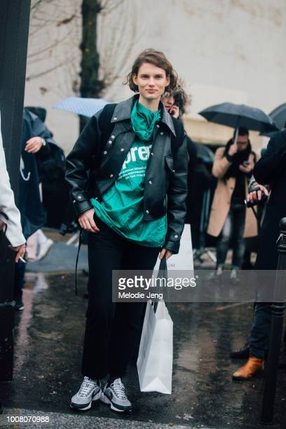 Model Giedre Dukauskaite wears a black leather jacket green Supreme top and white Nike sneakers after the Celine show a Tennis Club de Paris during...