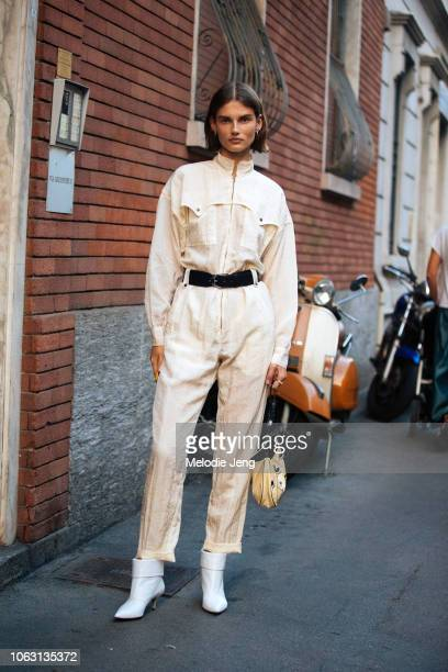 Model Giedre Dukauskaite wears a cream jumpsuit witha belt and white boots during Milan Fashion Week Spring/Summer 2019 on September 19 2018 in Milan...