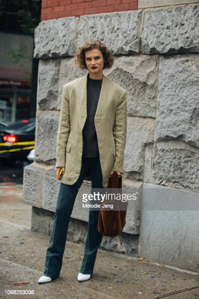 Model Giedre Dukauskaite wears a green blazer blue pants and a brown fur totême bag and white Paul Andrew shoes after the Escada show during New York...