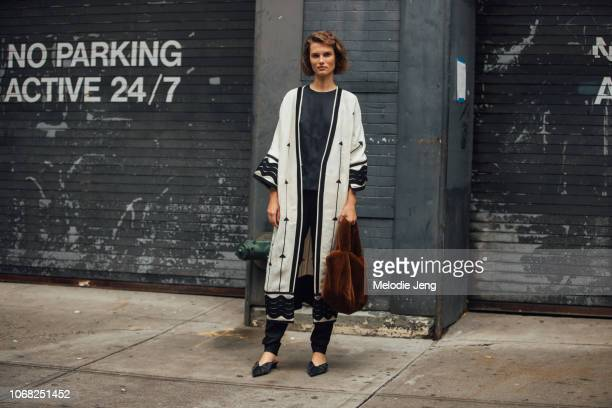 Model Giedre Dukauskaite wears a long white jacket brown Toteme fur bag and black shoes after the Gabriela Hearst show during New York Fashion Week...