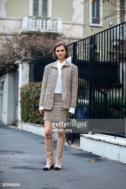 Model Giedre Dukauskaite wears a matching gingham blazer and skirt carries a black Bulgari bag and wears Chanel boots during Milan Fashion Week...